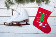 Skates and christmas sock and pine branches on a background of w