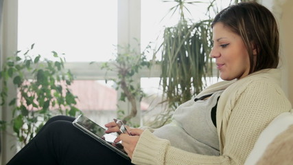 Young pregnant woman buying on line with credit card