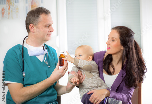 pediatric doctor giving pills bottle to mother with baby