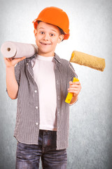 cute boy with a roll of wallpaper and brush