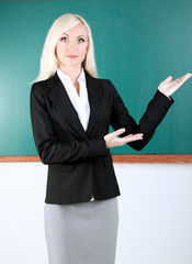School teacher near blackboard in classroom