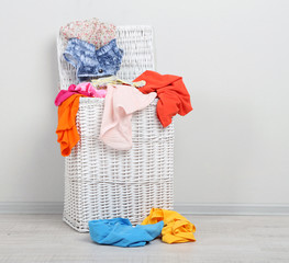 Full laundry basket  on wooden floor on gray background