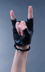 Hand of rocker in bracelet and leather mitten,