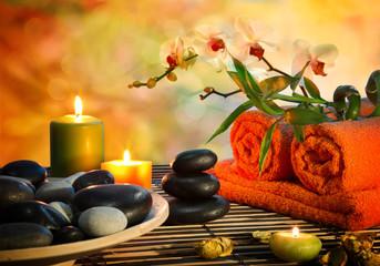 preparation for massage in orange lights and black stones