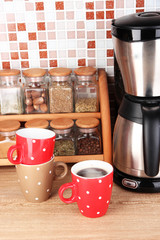 Cups and coffee maker in kitchen