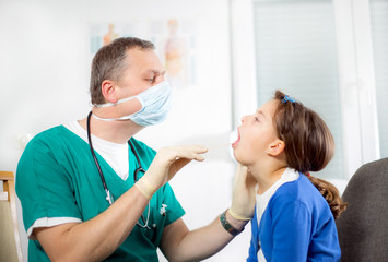 Doctor examining a girl's throat using a tongue depressor