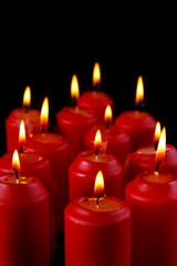 Burning red candles with black background