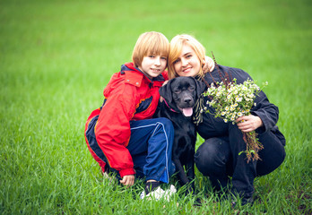 Happy family with Labrador is resting in the park
