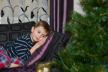 Cute boy looking at christmas tree