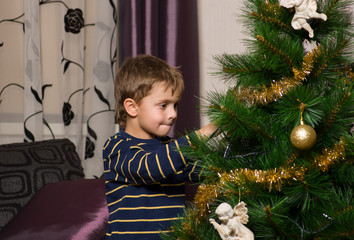 Cute boy decorating the christmas tree