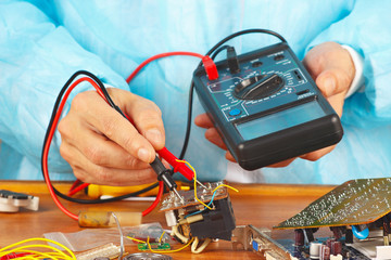 Serviceman checks electronic board with a multimeter