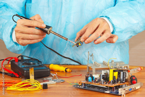 Serviceman solder electronic components of device in workshop