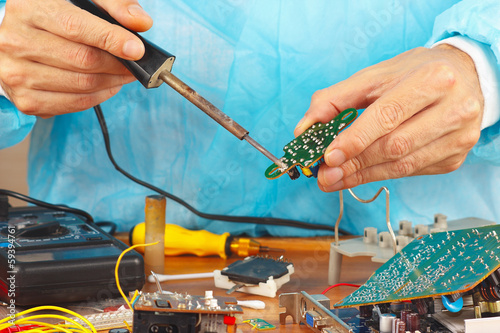 Repair electronic board of device with a soldering iron