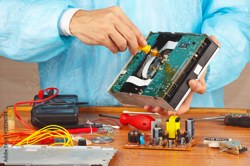 Master parses electronic device for repair in service workshop
