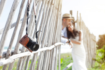 Photo camera on a fence against the sea and couple