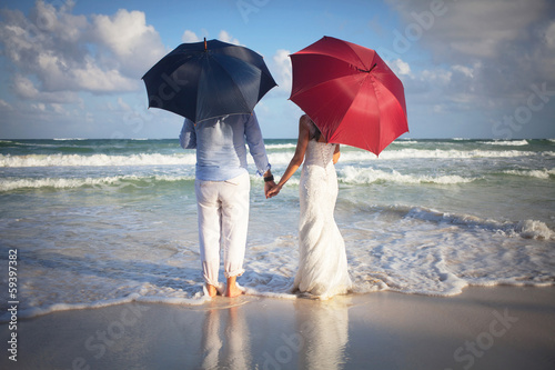 Beautiful couple of newly married stand on the beach with umbrel