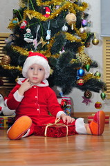 Boy with a gift under the Christmas tree