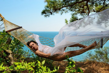 Girl in a hammock on a tropical coast