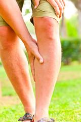 man rubbing his injured leg