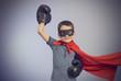 Superhero kid wearing boxing gloves
