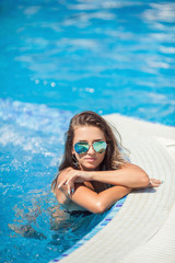 Beautiful woman resting near swimming pool on tropical resort