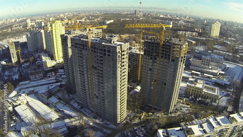 Houses under construction with cranes. Aerial