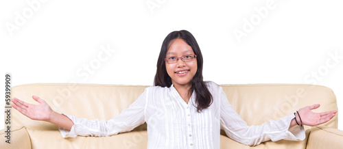 Teenage Asian girl with hand outstretched on a sofa