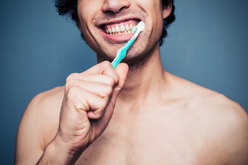 Happy young multi racial man brushing his teeth
