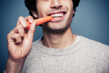 Young man eating a carrot