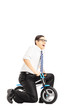 Excited young businessperson riding a small bicycle