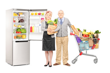 Couple holding a bag and shopping cart full of groceries