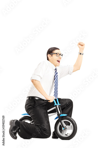 Excited young businessperson riding a small bicycle gesturing