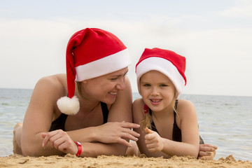 girl with her mother in a santa hat on the beach