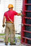 Construction worker assembling cement formwork poster
