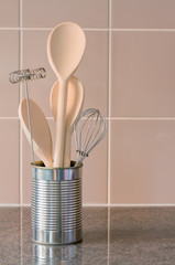Kitchen utensils in a can with tile background
