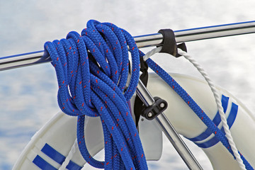 Rope being used to attach life preserver to boat rail
