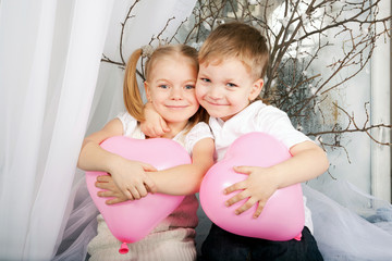 Little kids hugging and holding heart balloons.