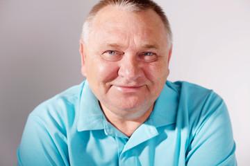 Smiling senior man closeup over white
