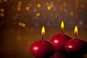 red christmas candles on golden bokeh background