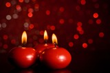 red christmas candles on red bokeh background