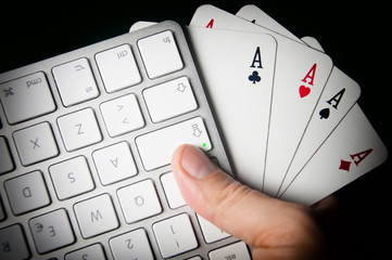 Poker On-line. Keyboard and four aces in hand.