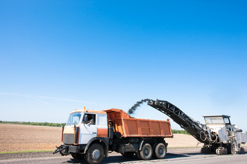 Milling machine loading worn asphalt into Dump Truck