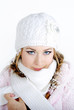 The young beautiful girl in a white cap and a scarf with snowfla