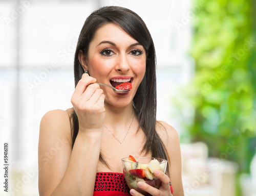 Woman eating a fruit cocktail