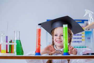 Smiling little chemist posing with colorful flasks