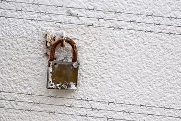 Candado en la pared con sombra del alambre de espino
