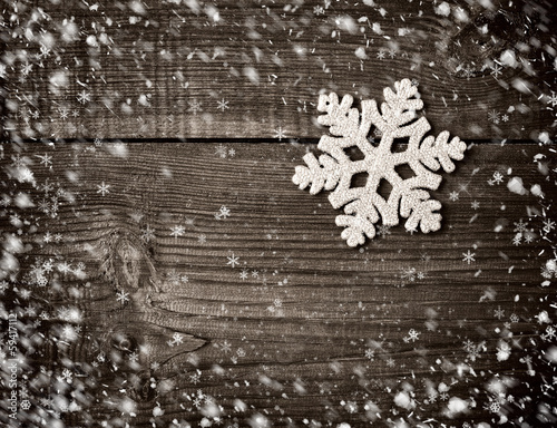 Snowflake on a snowbound old wooden background