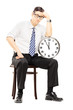 Sad male sitting on a wooden chair and holding a clock