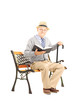 Senior man sitting on a wooden bench with a book