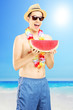 Young smiling man eating a slice of watermelon on a beach